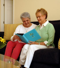 caregiver and elderly reading a book